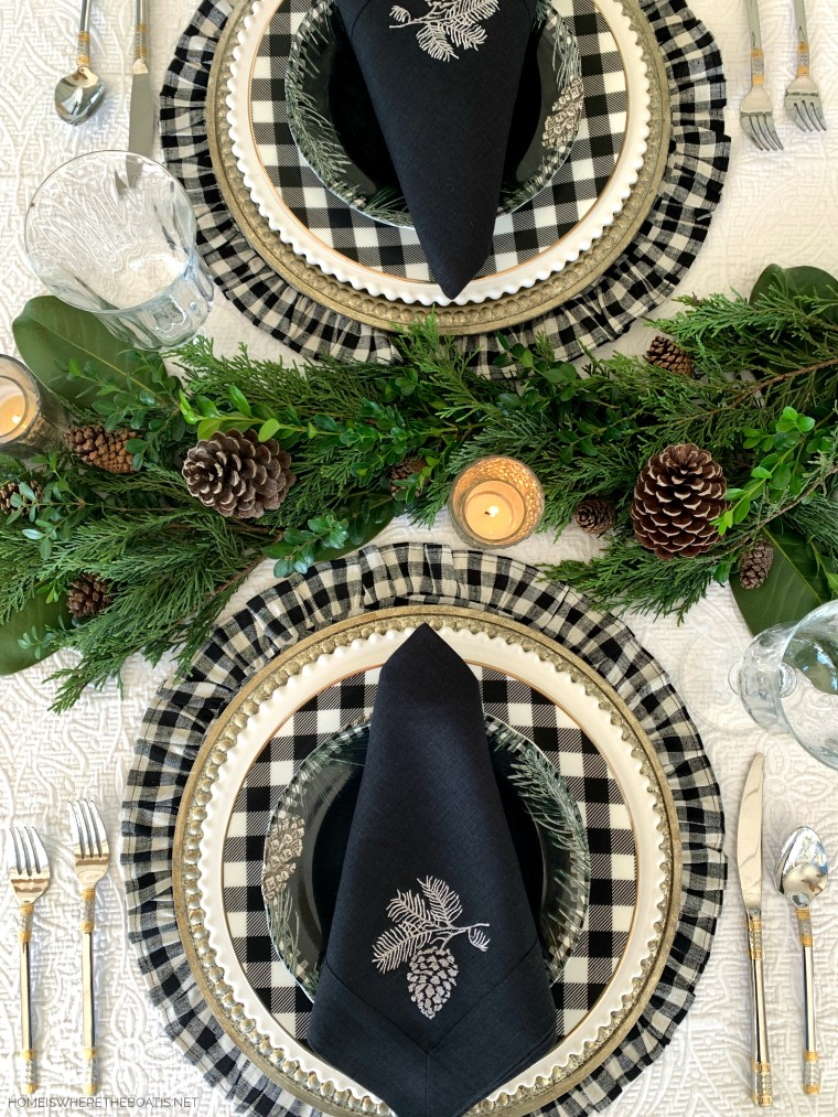 Christmas tablescape with Crown Linen Designs pinecone napkins, evergreen runner and black and white checks | ©homeiswheretheboatis.net #christmas #tablescapes