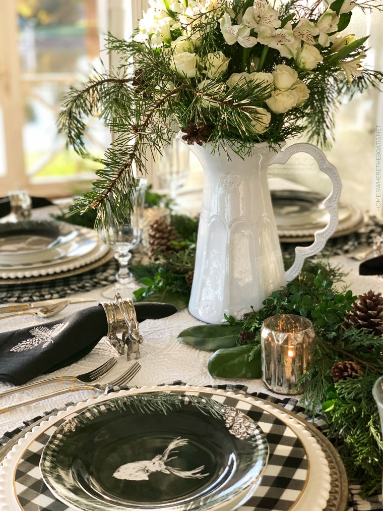 Christmas tablescape with evergreen runner, deer plates and black and white checks | ©homeiswheretheboatis.net #christmas #tablescape
