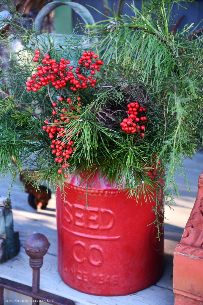 Red seed company pot with greenery for Christmas | ©homeiswheretheboatis.net #shed #christmas #garden
