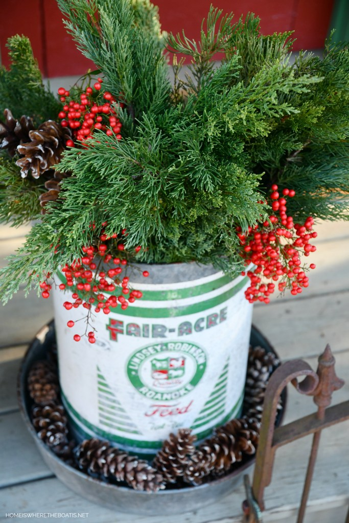 Vintage Fair-Acre Feed chicken feeder filled with greenery, pine cones and Nandina berries for Christmas | ©homeiswheretheboatis.net #shed #christmas #greenery