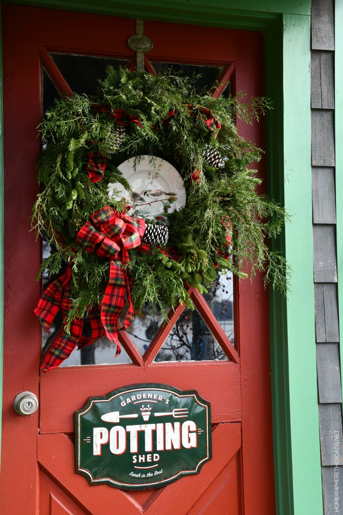 Evergreen wreath with bird plate and tartan ribbon on Potting Shed door for Christmas | ©homeiswheretheboatis.net #shed #christmas #wreath