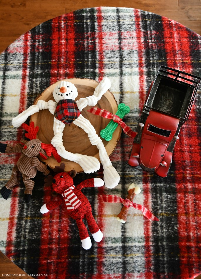 Whimsical Dog Toys and Treats Table with Red Truck | ©homeiswheretheboatis.net #christmas #table #redtruck #dogs #plaid #tartan