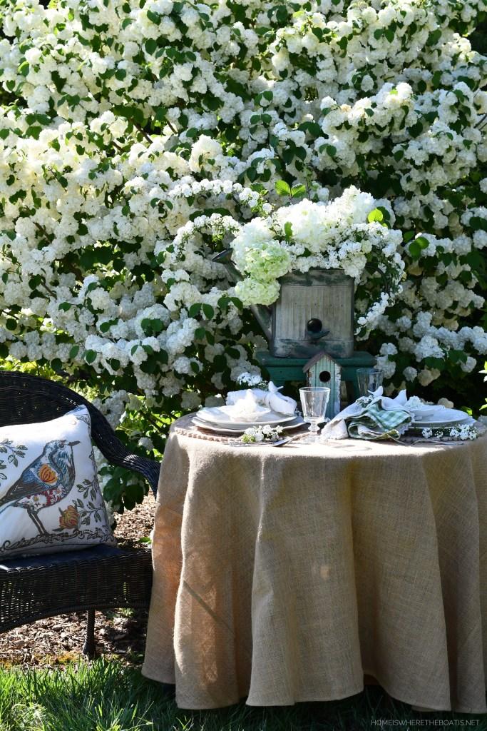 Garden spring table with birds and Snowball Viburnum | ©homeiswheretheboatis.net #spring #flowers #garden #tablescape #alfresco