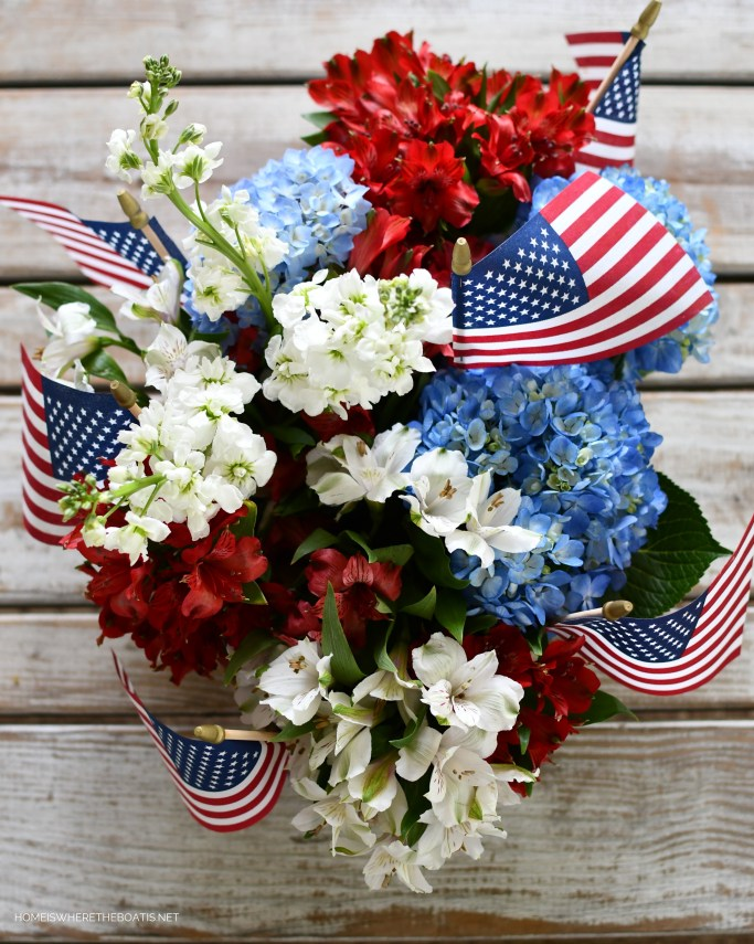 Boat caddy with flowers and flags for nautical table centerpiece | ©homeiswheretheboatis.net #patriotic #nautical #lake #tablescapes #redwhiteandblue