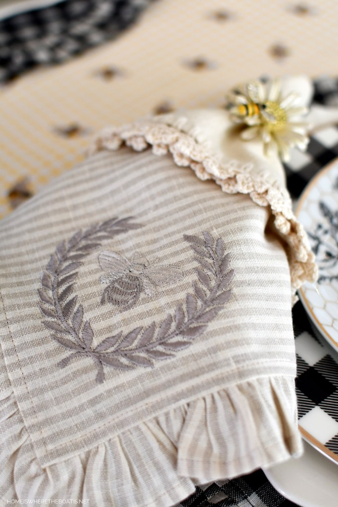 Buzzing with Bees: Embroidered bee with laurel wreath napkin and tablescape | ©homeiswheretheboatis.net #flowers #DIY #tablescape #bees #sunflowers #summer