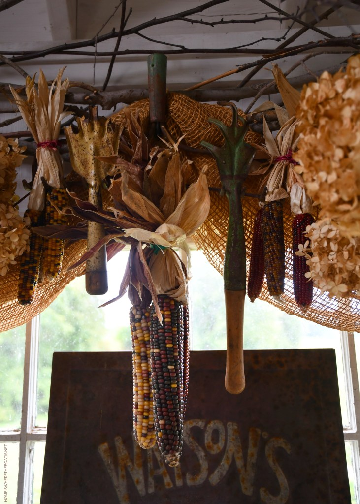Indian corn and vintage garden tools hanging on rake in the Potting Shed | ©homeiswheretheboatis.net #garden #fall #harvest #tablescape #pottingshed