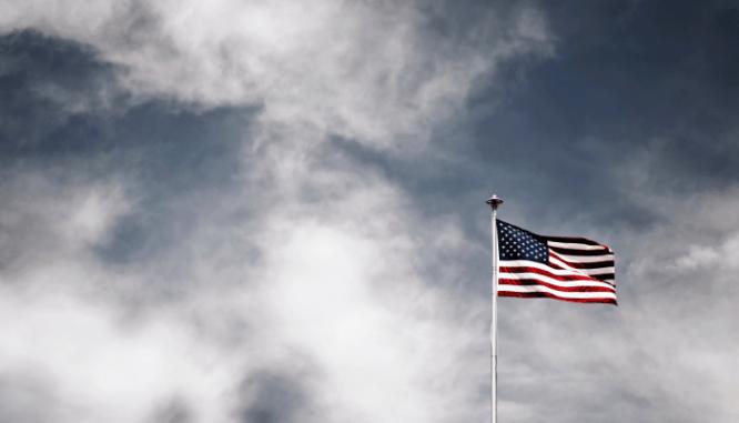 An American flag near an affordable house.