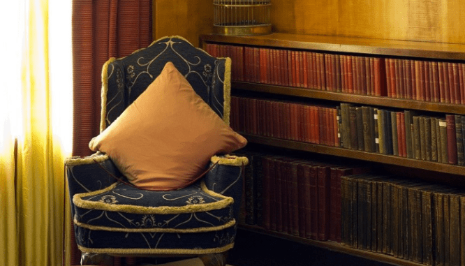 A chair and book shelf with art deco interior design.
