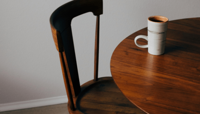 An image of a wooden table used to demonstrate the process of furnishing a new home.