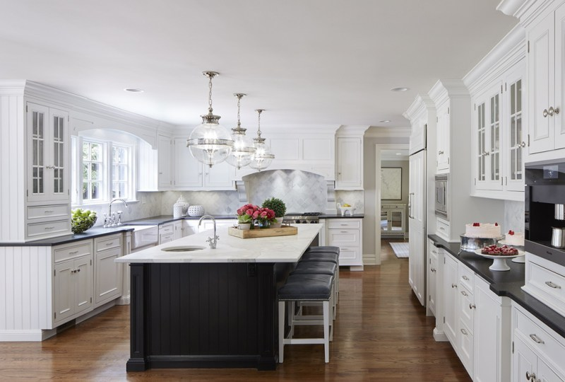 White kitchen with black countertops. Kitchen with modern globe pendant lights over black kitchen island with white marble countertop