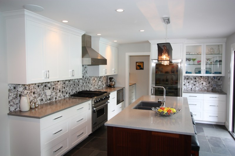 White kitchen with gray tile flooring. Kitchen with linear crystal chandelier over wooden kitchen island with white laminate countertop
