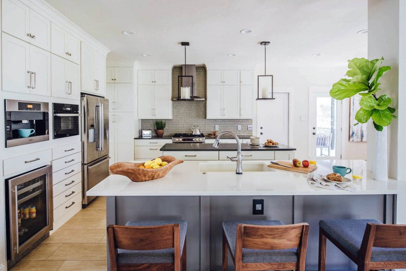 White kitchen with with white cabinets and bar stools. Kitchen with candle pendant lights over wooden kitchen island with black laminate countertop