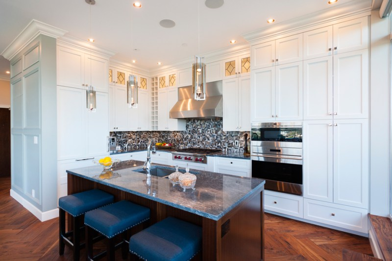 White kitchen with navy bar stools and gray backsplash. Kitchen with tube pendant lights over wood kitchen island with marble countertop