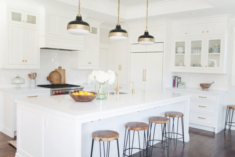 White kitchen with wood and iron bar stools. Kitchen with black gold pendant lights over white kitchen island with marble countertop