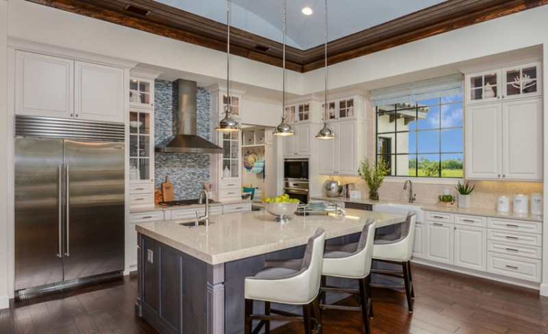 White kitchen with white swivel bar stools. Kitchen with chrome pendant lights over gray kitchen island with marble countertops