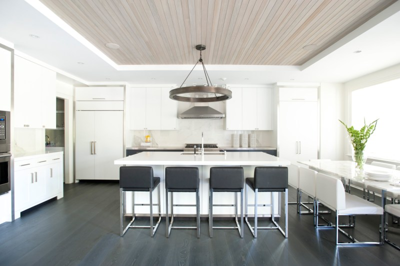 White kitchen with dark oak wood floors. Kitchen with round chandelier over white kitchen island with laminate countertops