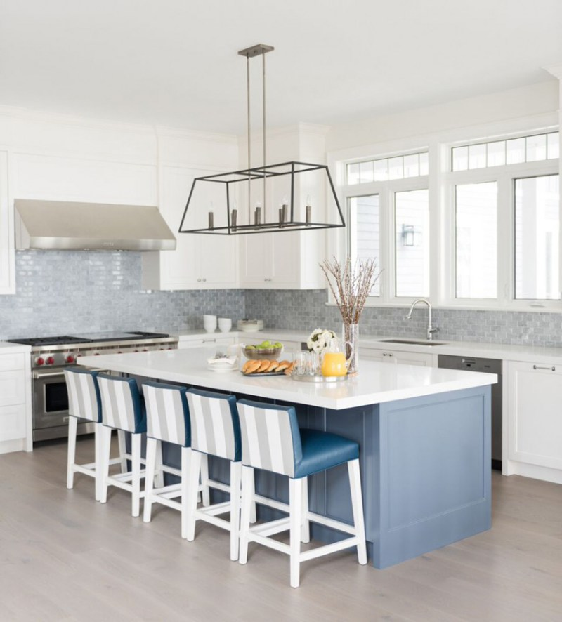 White kitchen with gray glass tile backsplash. Kitchen with box cage pendant lights over blue kitchen island with white laminate countertop