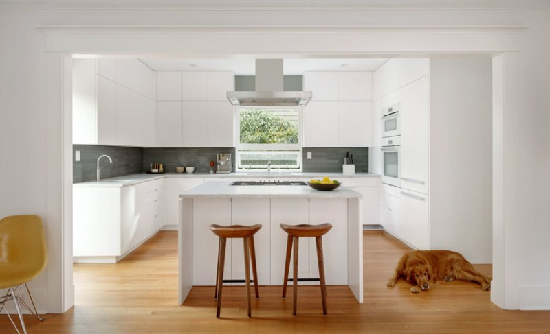 Modern white kitchen with wooden bar stools. Kitchen with gray backsplash , white kitchen island and light wood flooring