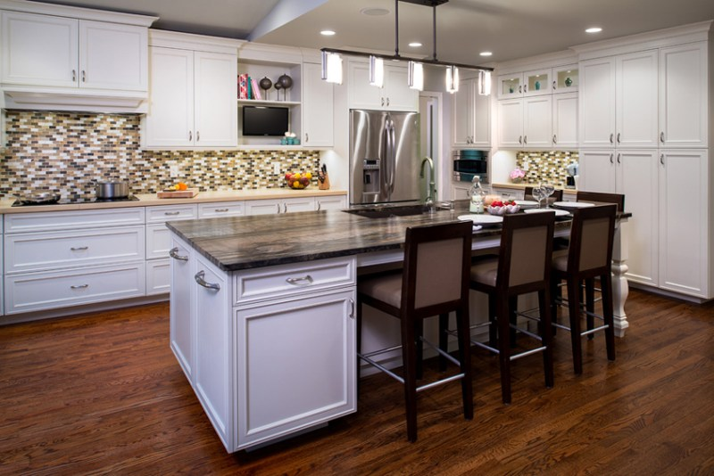 White kitchen with mosaic subway tile backsplash. Kitchen with track pendant lights over white kitchen island with wooden countertop