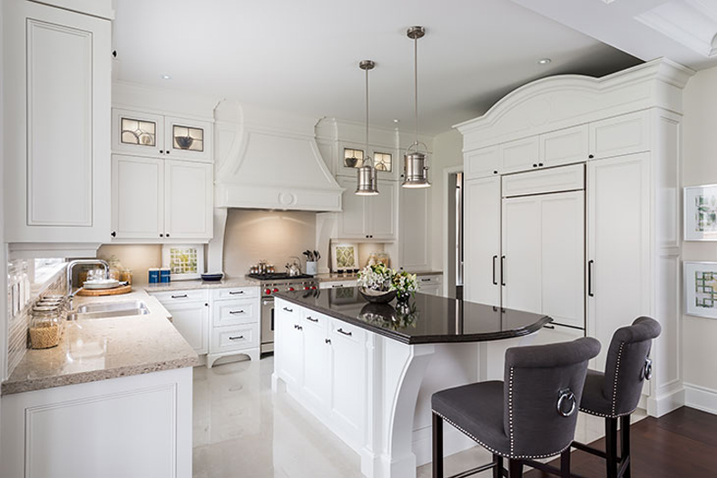 Classic white kitchen with vinyl flooring. Kitchen with chrome pendant lights over white kitchen island with black laminate countertop