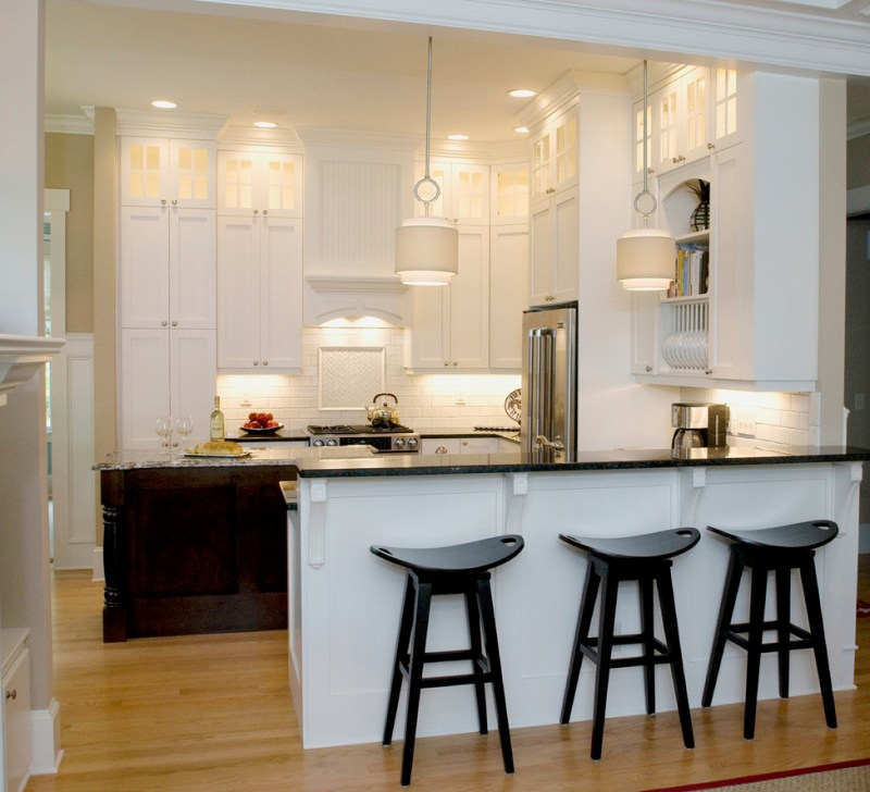 Small white kitchen with under cabinet lighting. Kitchen with black bar stools and drum shade pendant lights