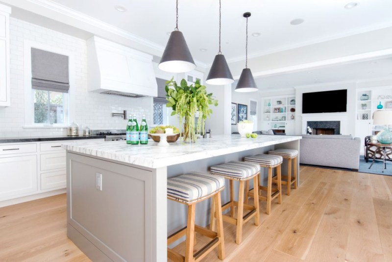 White kitchen with white tile backsplash and backless bar stools. Kitchen with contemporary pendant lights over gray kitchen island with marble countertop
