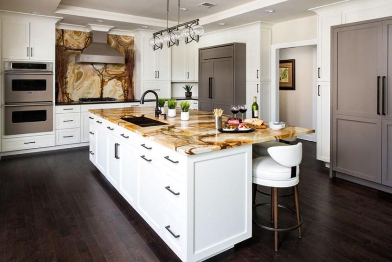 White kitchen with wood stone granite backsplash. Kitchen with track pendant lights over white kitchen island with stone wood granite countertop