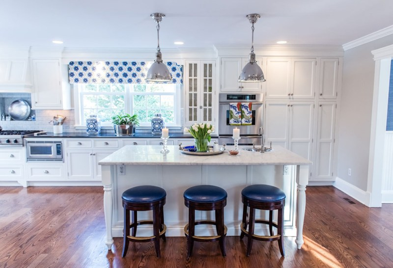 White kitchen with navy blue bar stools. Kitchen with laminate wood flooring and chrome pendant lights over white kitchen island