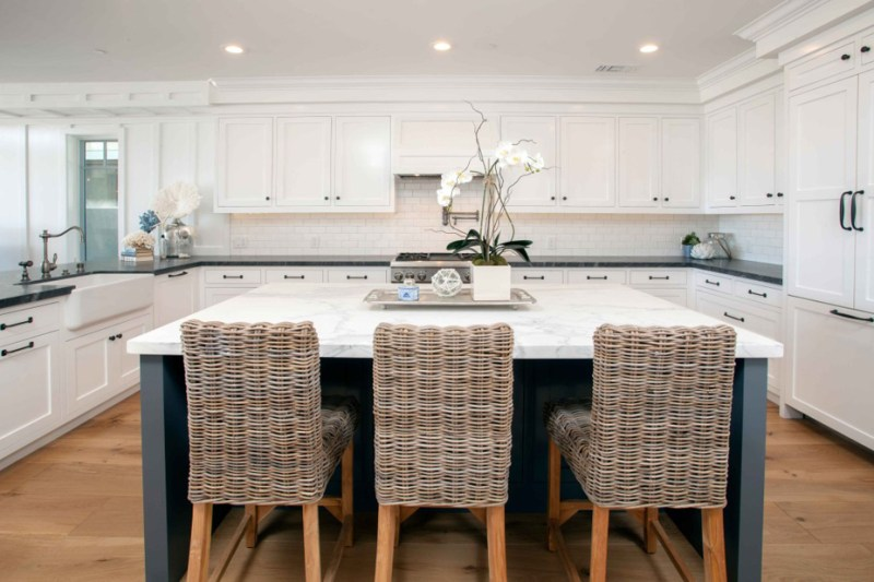 White kitchen with wicker rattan bar stools. Kitchen with large kitchen island with white cabinet