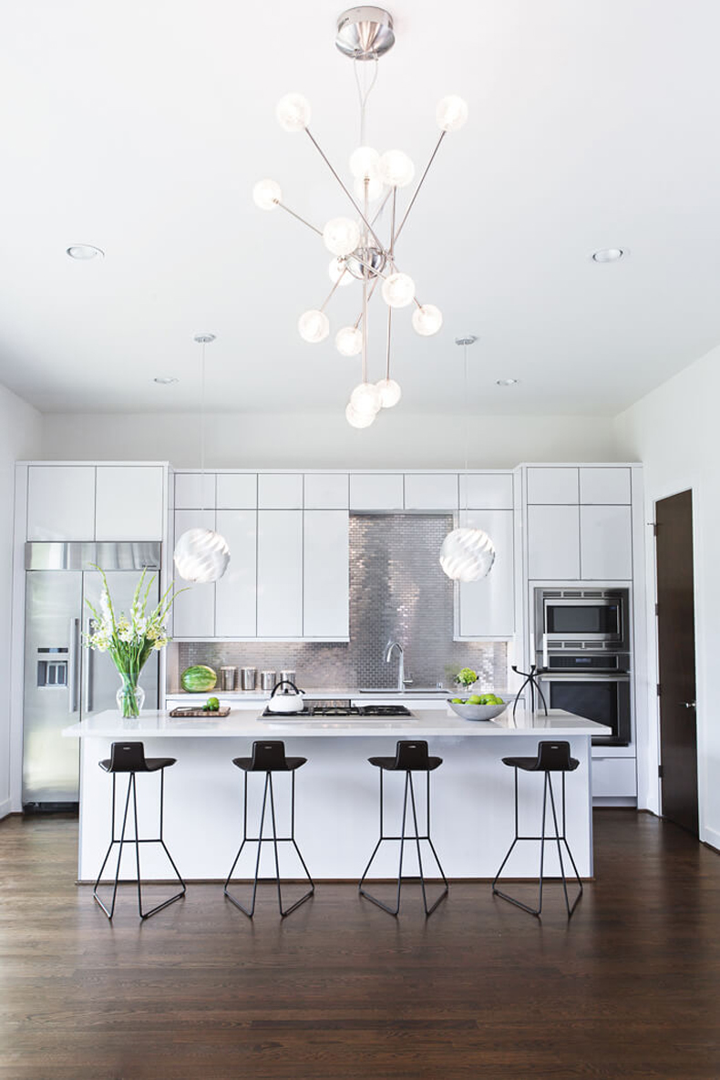 White kitchen with industrial bar stools and dark hardwood flooring. Kitchen with modern hanging globe pendant lights over kitchen island with marble countertops