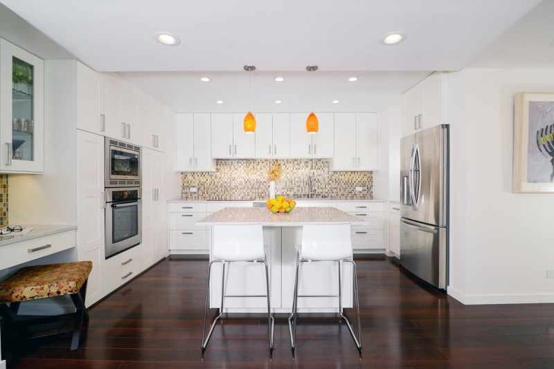 White kitchen cabinets with dark hardwood floors. White kitchen with orange pendant lights over kitchen island with marble countertops