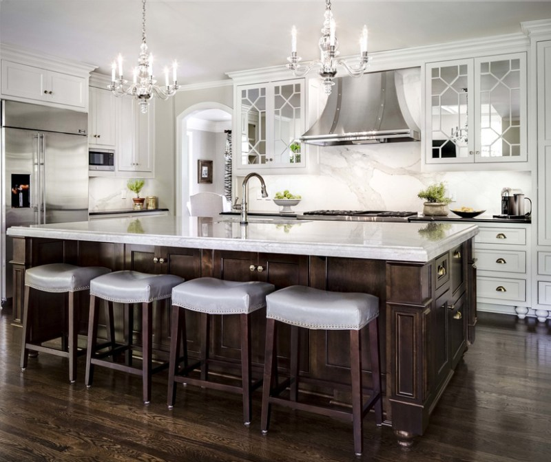 White kitchen with gray leather bar stools. Kitchen with mini candle chandeliers over wooden kitchen island with white countertop