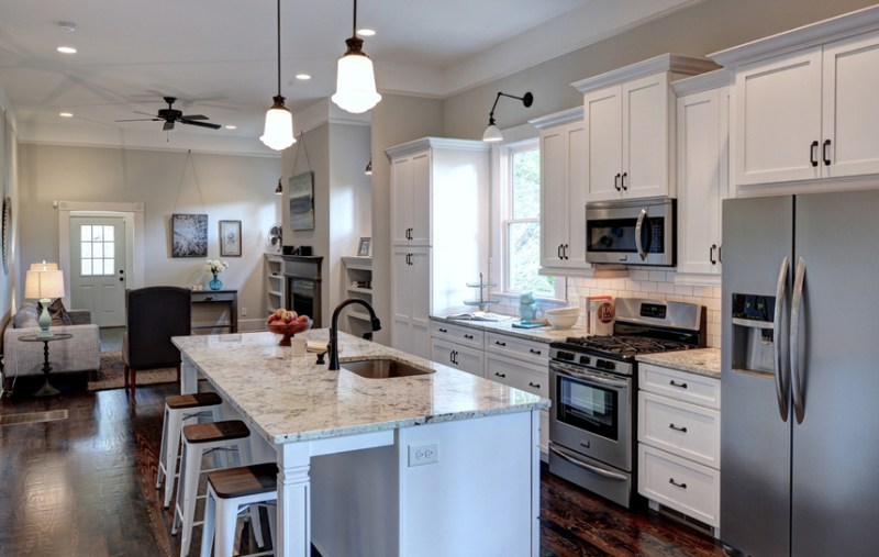 White kitchen with short bar stools and hardwood floors. Kitchen with mini pendant lights over kitchen island with marble countertop