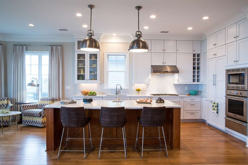White kitchen with mid century bar stools. Kitchen with nickel dome pendant lights over wooden kitchen island with marble countertop