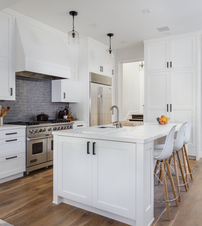 White kitchen with gray brick tile backsplash. Kitchen with mini pendant lights over white kitchen island with marble countertops