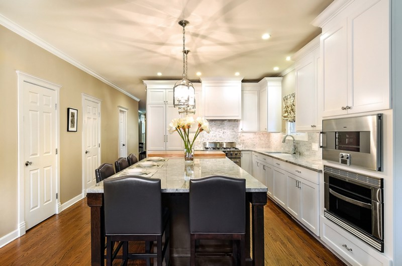 White kitchen with black leather bar stools. Kitchen with lantren pendant lights over kitchen island with marble countertop