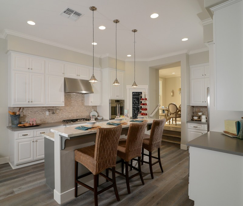 White kitchen with rattan wicker barstool. Kitchen with mini pendant lights over kitchen island with marble countertop