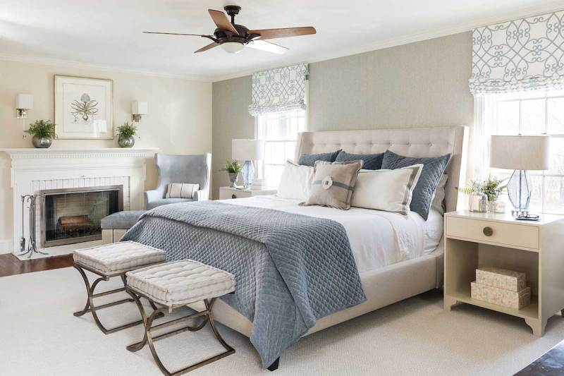 master bedroom with ceiling fan and wall sconces