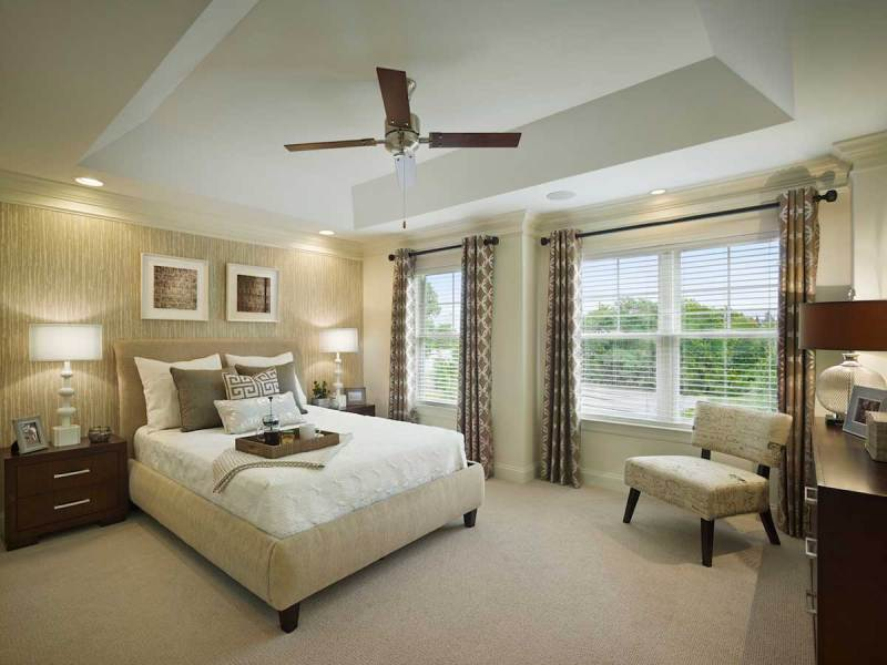 modern bedroom with table lamps and ceiling fan lighting
