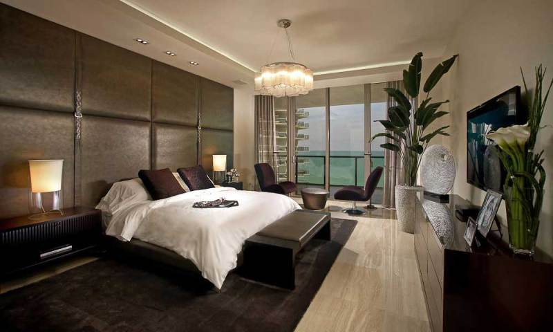modern master bedroom with drum shade chandeliers and table lamps