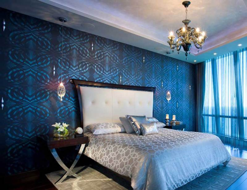 blue bedroom with gold chandelier and pendant lighting