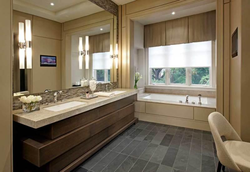 bathroom with tube wall sconces