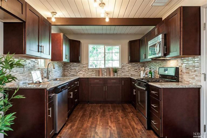 Craftsman kitchen with bianco antico countertops and cherry cabinets