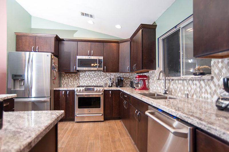 Brown kitchen cabinets with bianco romano granite countertops and backsplash