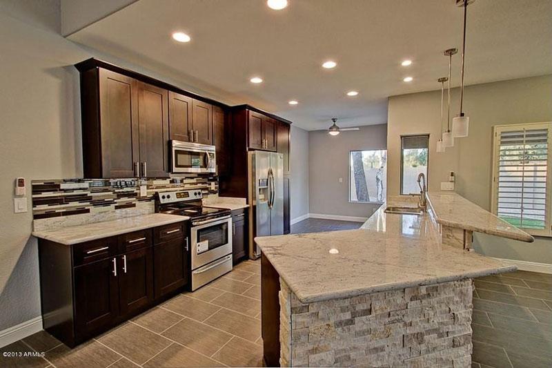 Black kitchen cabinets with bianco romano granite