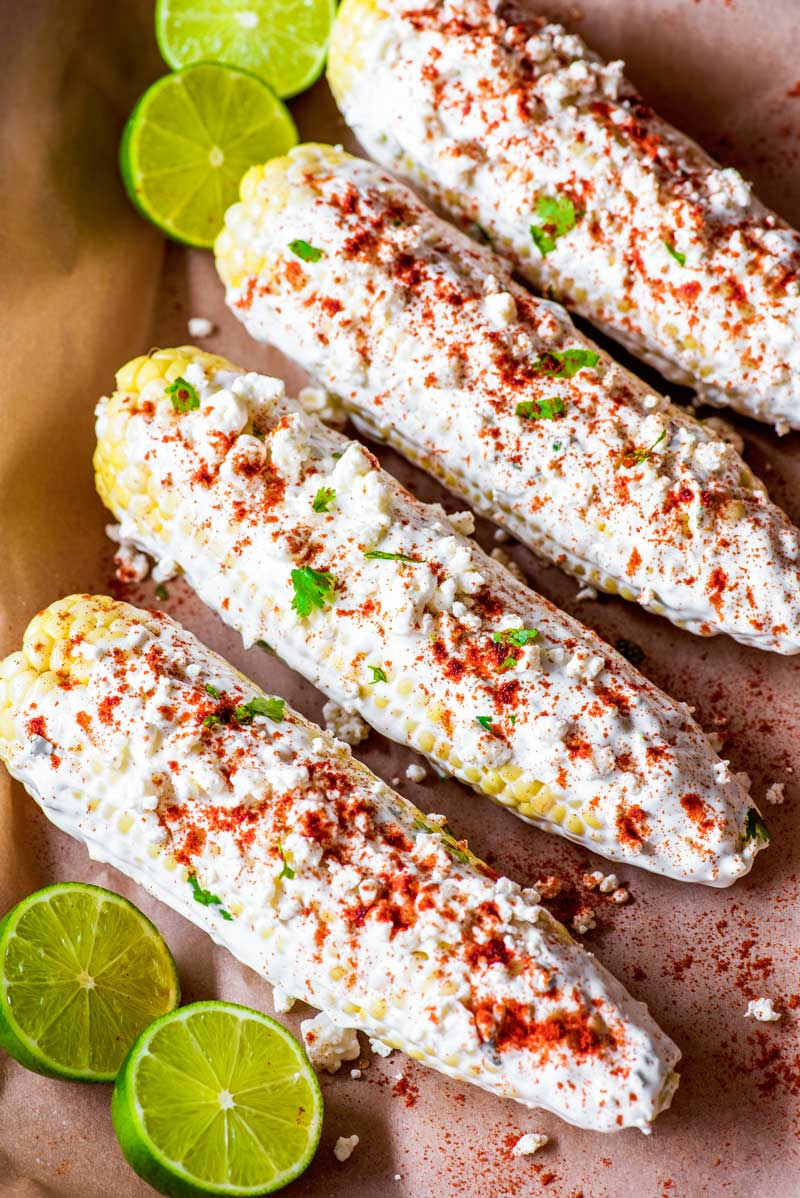 Baked Mexican Corn! Classic Mexican corn on the cob that's flavored with feta cheese and smoked paprika and makes for a perfect appetizer, side dish, or simple dinner. Plus, this Mexican street corn is baked, so it's easy to whip up this summer favorite all year long!   HomemadeHooplah.com