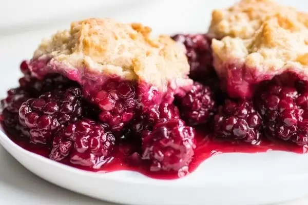 Two scoops of blackberry cobbler on a white plate