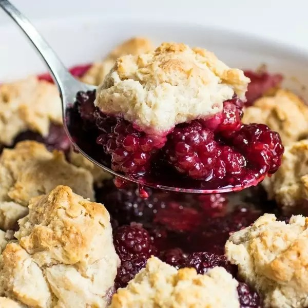 A big piece of blackberry cobbler on a spoon