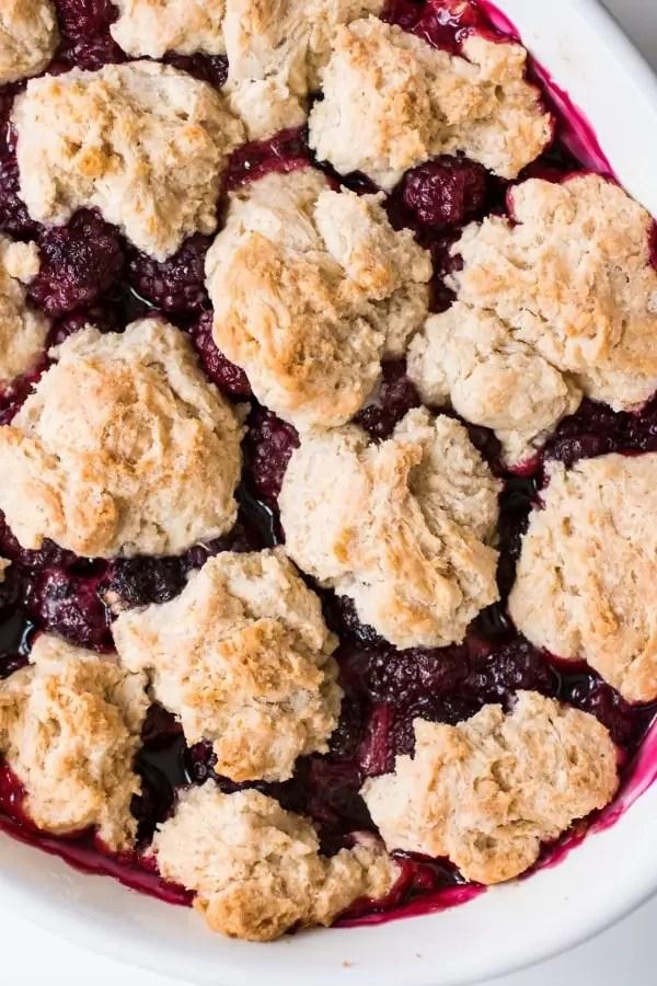 Golden brown drop biscuits baked on top of fresh blackberry cobbler