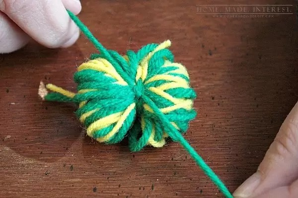 This simple craft tutorial on how to make yarn pom poms will change your life! You'll want to put yarn pom poms everywhere! They are great for party decorations, garlands and banners, and cupcake toppers!
